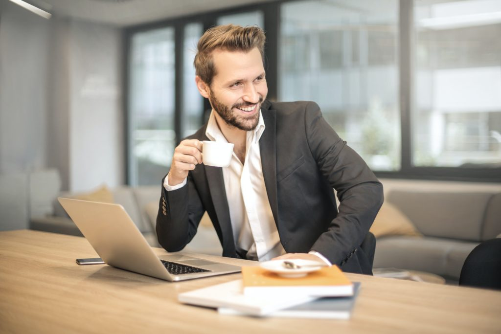 man holding white teacup in front of gray laptop 842567