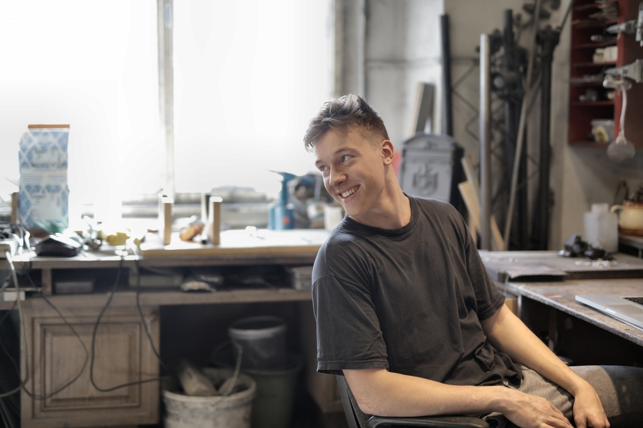 cheerful man sitting at table in workshop 3844524