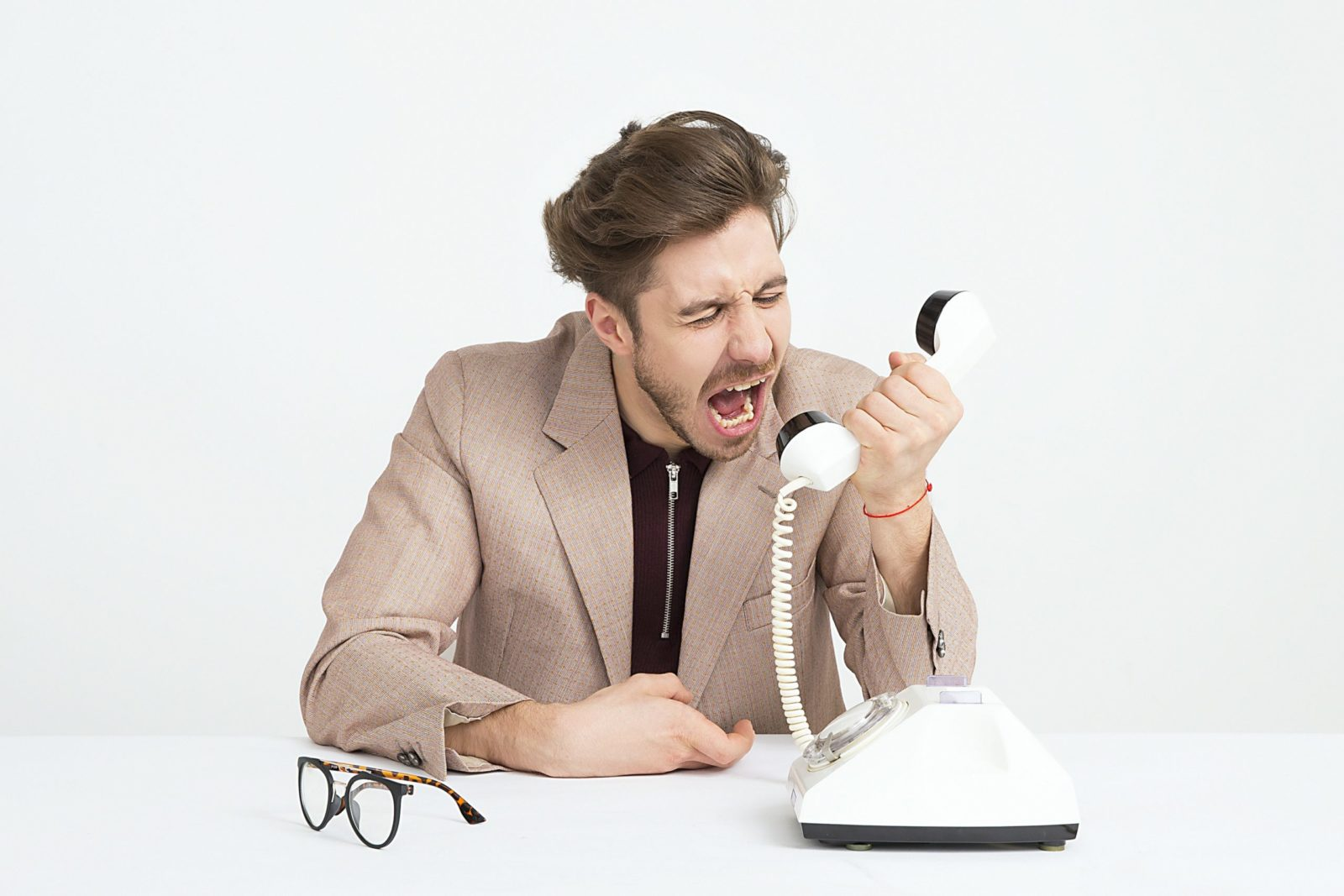 man wearing brown suit jacket mocking on white telephone 1587014 scaled